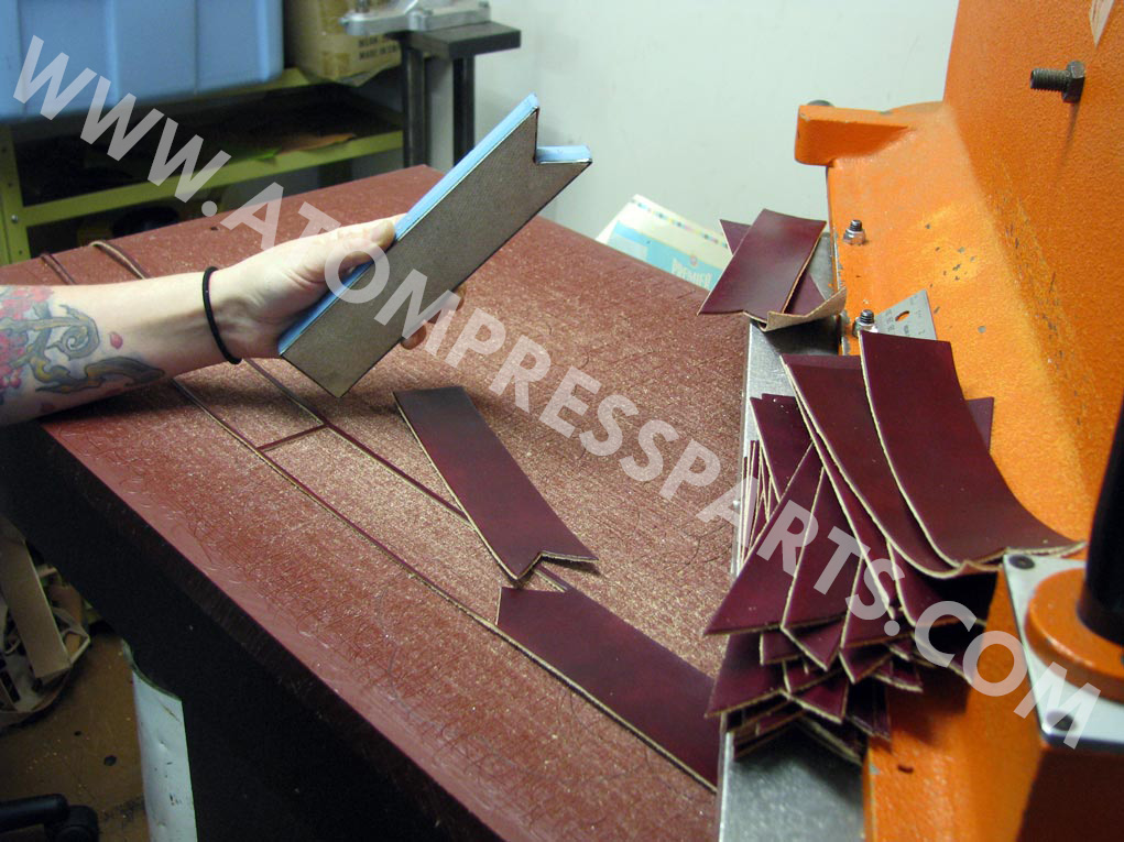 a man holding a die cut with pieces of ribbon shape objects in the table with swing arm press